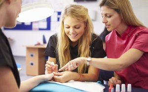 Photo of Cosmetology Student doing nails on a client with instructor helping