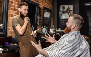 Photo of a barber talking the client in his chair